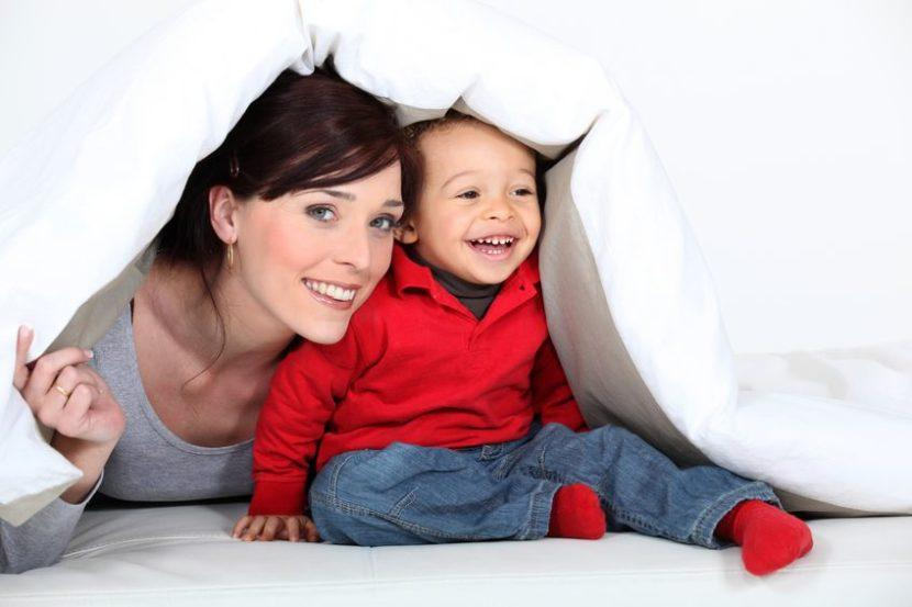 17732550 - woman and child hiding under a duvet
